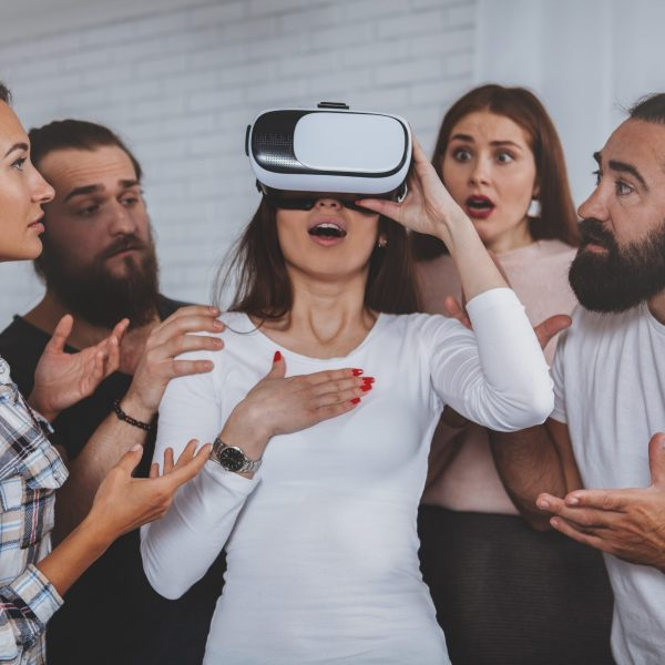 Young woman looking overwhelmed and shocked, wearing virtual reality headset, her friends surrounding her. Group of businesspeople working together on innovative project, using vr goggles